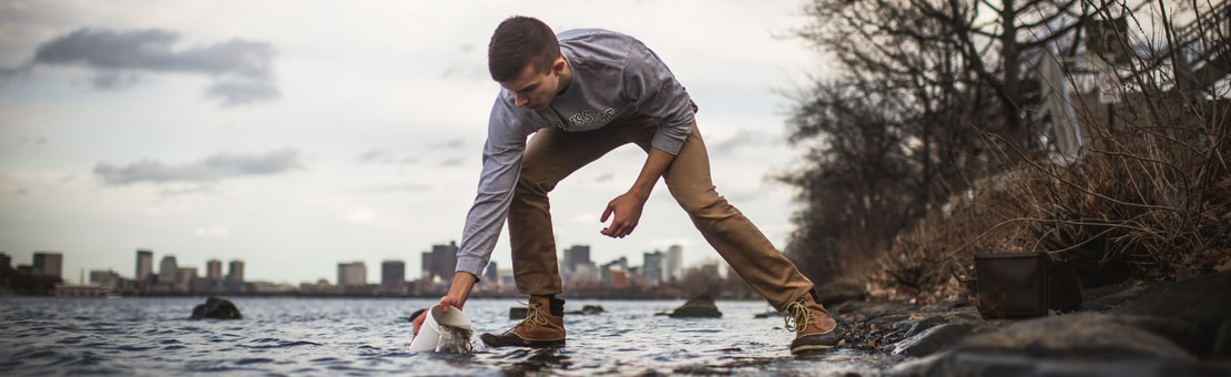 Student taking water sample from Charles River