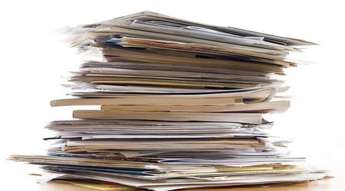 a stack of papers and manilla folders